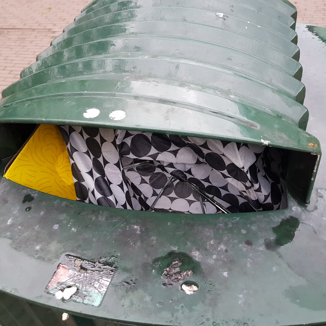 Black and white Brolly in a green Bin.