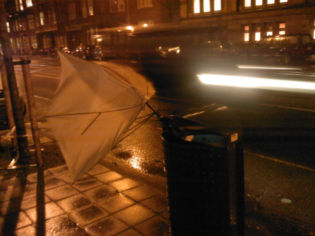 Nightly photo of a binned brolly, almost fly out because of wind