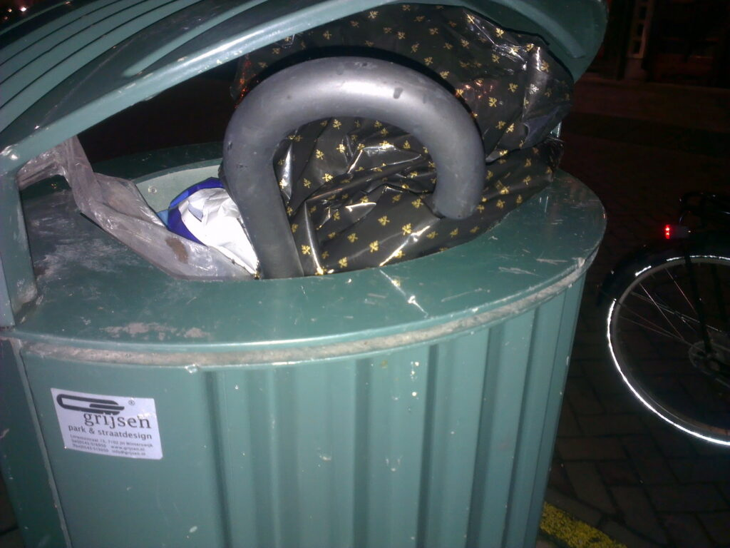 Nightly photo of a binned brolly, only the crook handle is visible