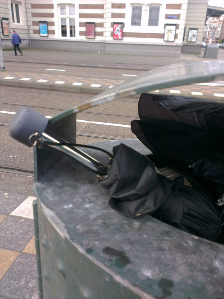 2 binned brollies, both black and one with a printed weed leaf. In one picture the Concertgebouw is clearly visible.