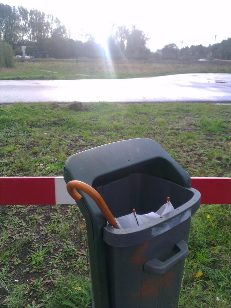 A white binned brollie in front of a unused road and some wild land. The handle is in wood colour but probably plastic.