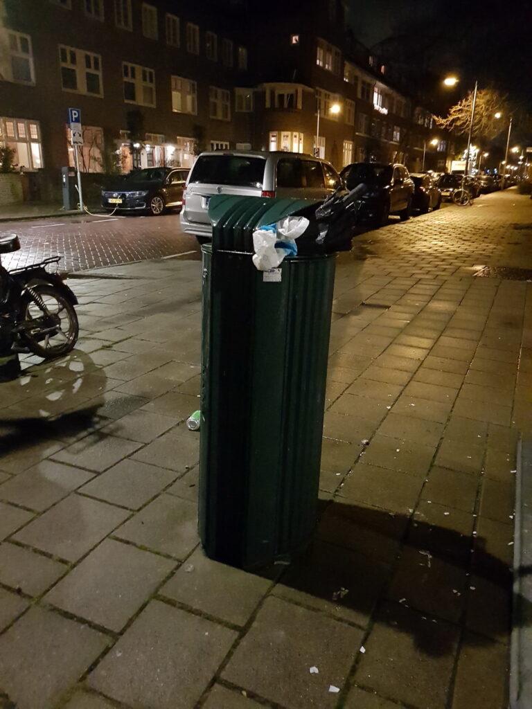 Nightly photo of a binned brolly, near a moped. Street still wet from rain