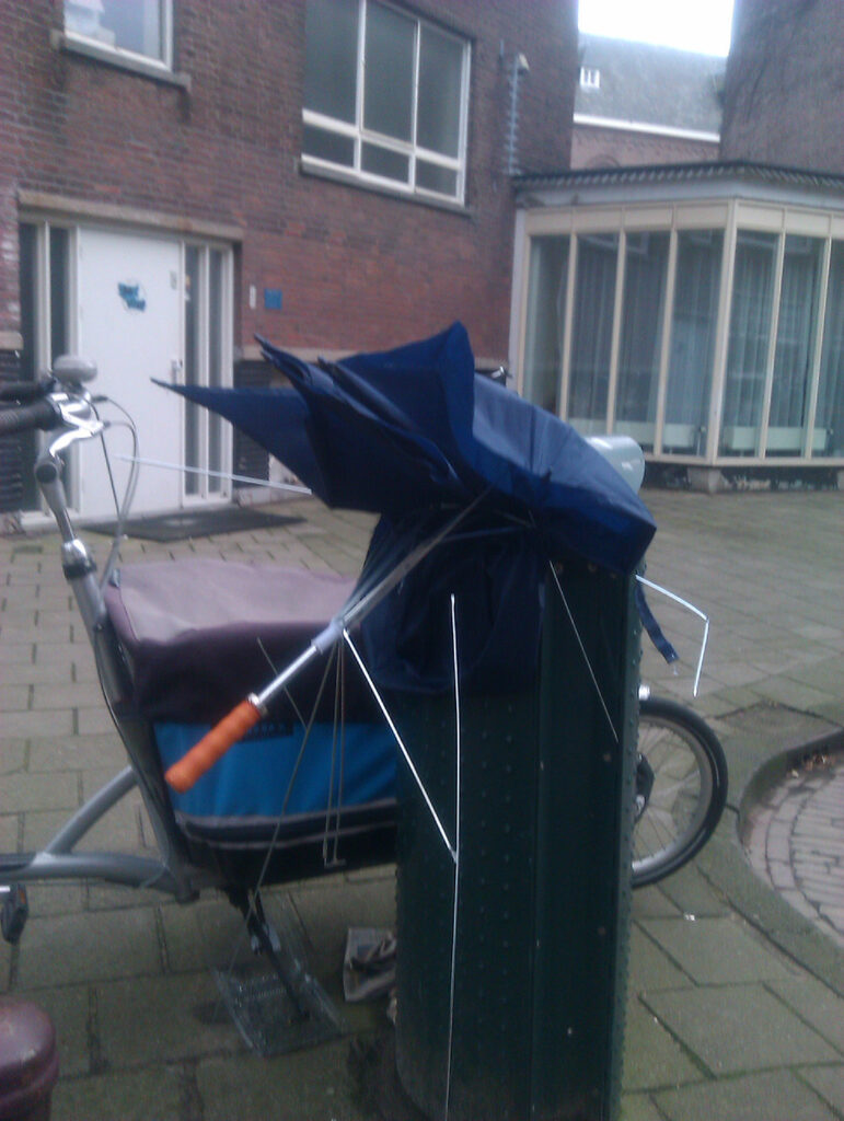 Blue brolly stuffed in city bin. Bin in front of a cargo bike.