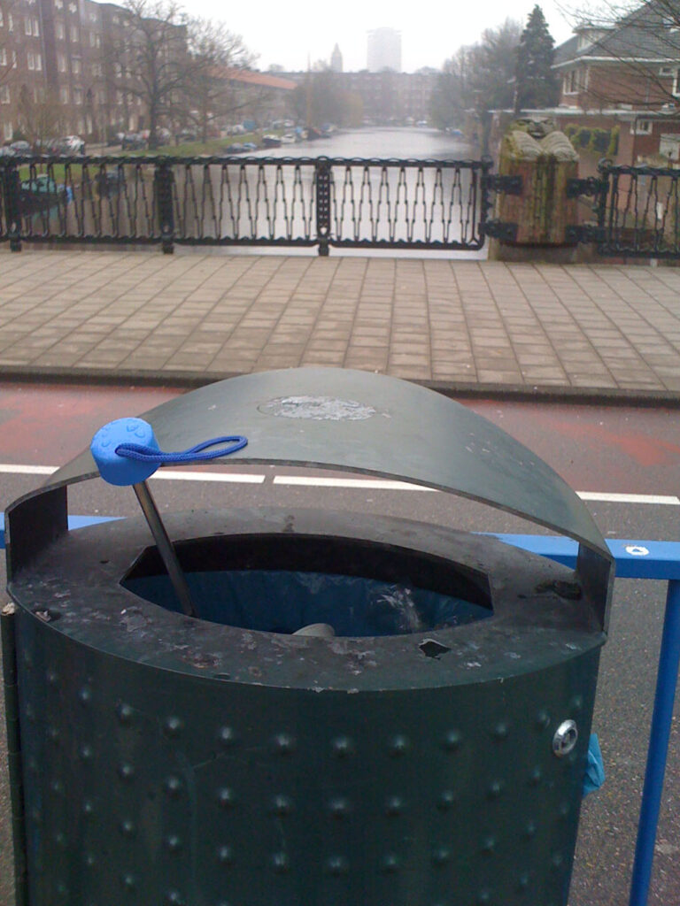One brolly with blue handle in a bin and one black brolly next to it. Bin is on a tram stop which it self is on a Amsterdam bridge.