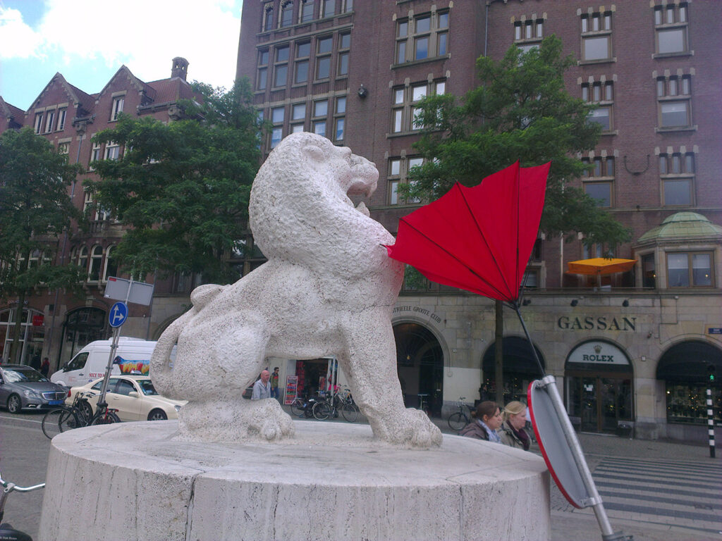 """Statue of a lion """"scares"""" of a broken red brolly stuck in a traffic sign"""