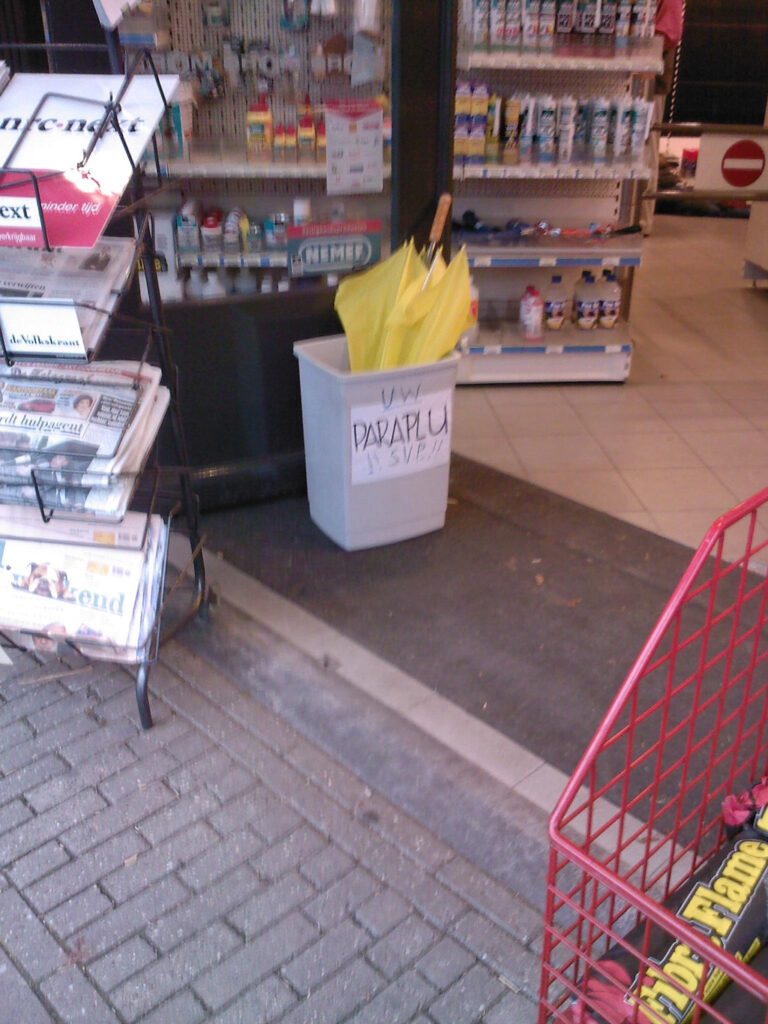 A yellow brolly in a bin (used as a umbrella stand) in front of a shop