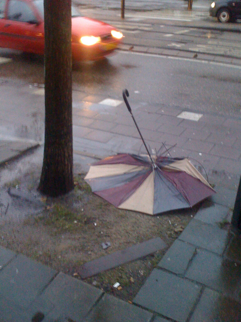 Brolly between tree and bin, all panels are flat on the ground. Tri colour fabric, upside down. Rain poors.