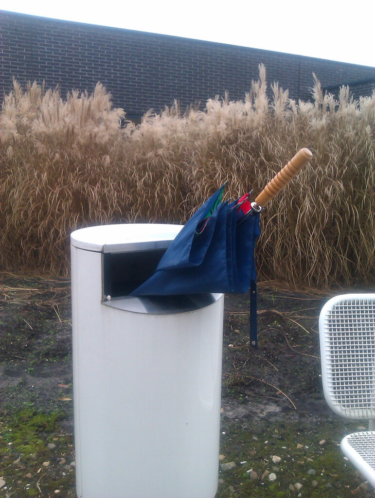 A perfect Bin Brolly, sticking out for a rather big part. White bin. Blue, red and green brolly.