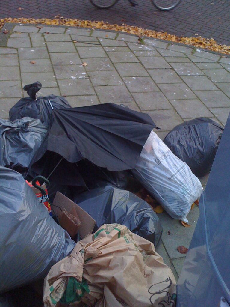 Dumbed broken brolly on a pile of garbage. All on a corner of a street.